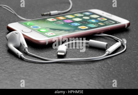 Koszalin, Poland – February 22, 2017: Pink iPhone 7 on stone table. Devices displaying the applications on the home - Stock Photo