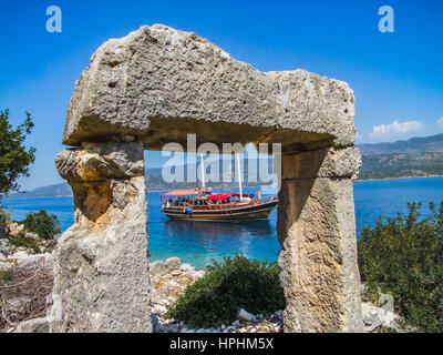 blue cruise boat passing by the island people on the boat watching the island and ruins, mavi yolculuk teknesi. - Stock Photo