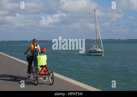 France, Vendee, Noirmoutier island, tourists riding bikes on Jacobsen's pier. - Stock Photo