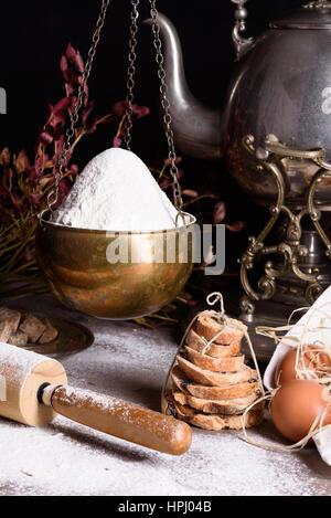 Bread baking ingredients - flour, eggs, baking powder. Baked flour-based food still life with antique teapot. - Stock Photo