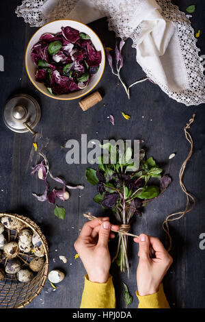 Herbs, gathered into a bunch and tied, over rustic table with salad and farm eggs. Overhead view. Healthy diet background. - Stock Photo