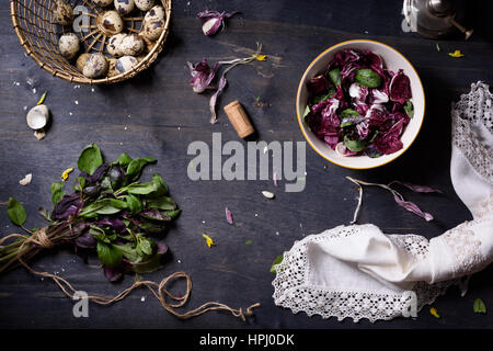 Fresh spring salad with basil, eggs, radicchio leaves and garlic on dark wooden table, top view. - Stock Photo