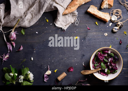 Healthy purple salad mix with fresh french bread over dark rustic wooden table, from above. Background layout with - Stock Photo