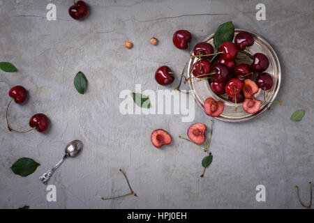 Cherry on a plate over grey rustic background, copy space, overhead view. Fresh berries, fruit. - Stock Photo