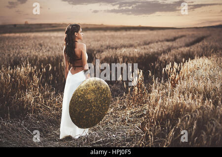 Back view of brunette girl with long hair wearing in white dress like greece style,  holding iron shield in hand. - Stock Photo