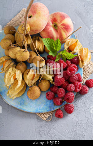 Tropical fruit plate with mango, raspberry, longan and peaches - Stock Photo