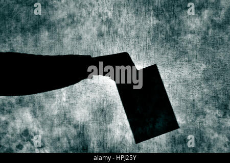 the shadow of a man man with an envelope in his hand behind a gray fabric, as he was voting - Stock Photo