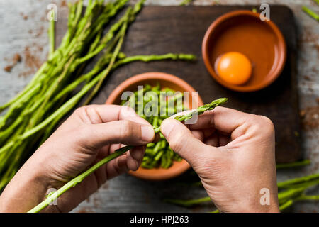 young man chopping wild asparagus with his hands and some earthenware bowls with chopped asparagus and a cracked - Stock Photo