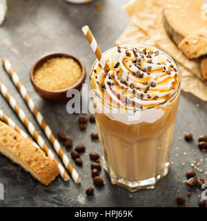 Iced caramel latte coffee in a tall glass with syrup and whipped cream - Stock Photo