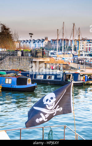 A boat flies the Jolly Roger in the foreground while narrowboats are moored behind in this scene of Bristol Harbour, - Stock Photo