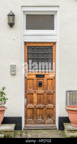 old style entrance to the building, pots with green plants, the entrance from the sidewalk to the building, a large - Stock Photo