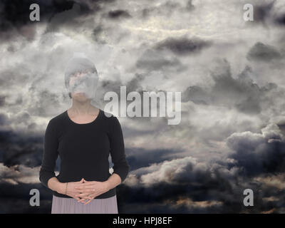 Woman in a dark space, grey clouds. Depression, anxiety concept, metaphor. - Stock Photo