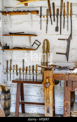 Vintage carpentry tools hanging on wall. - Stock Photo