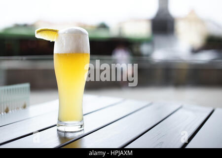 Glass of wheat beer with slice of lemon on a table outdoors in Minsk, Belarus - Stock Photo