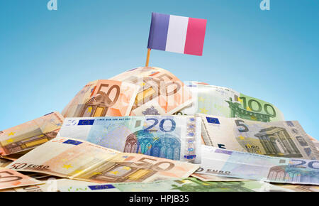 The national flag of French Guiana sticking in a pile of mixed european banknotes.(series) - Stock Photo