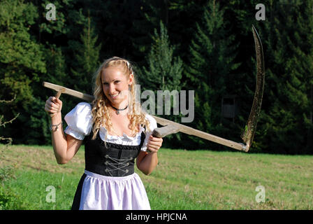 Model released , Junge Baeurin im Dirndl mit Sense - young woman in dirndl with scythe - Stock Photo