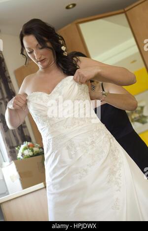 Braut beim Kleidanziehen - bride dresses up - Stock Photo