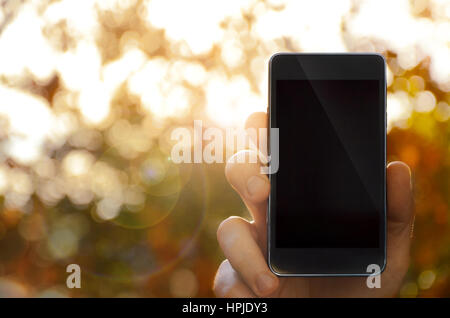 Man with smart phone on hand, blurred background.Image can be used for several purposes like: background, web banner, - Stock Photo