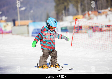 Little boy skiing downhill, wearing safety helmet and goggles - Stock Photo