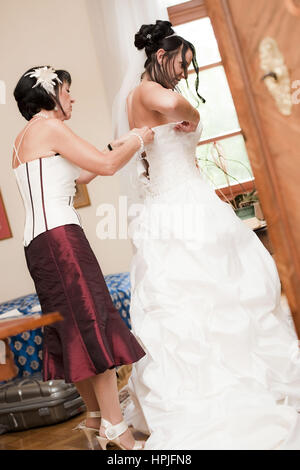 Model released , Braut beim Ankleiden - bride puts on clothes - Stock Photo