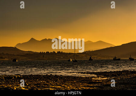 Cuillin Hills Mountain Range, across Loch Portree, on the Isle of Skye, Scotland, against a dramatic sky late evening - Stock Photo