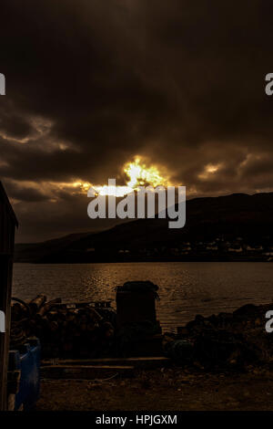 Winter afternoon sun across Loch Portree, looking toward Viewfield Road and the Black Cuillin mountains - Stock Photo