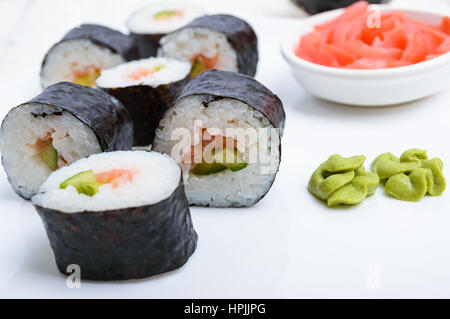 Traditional eastern dish with salmon sushi rolls on a white plate. Close-up. - Stock Photo