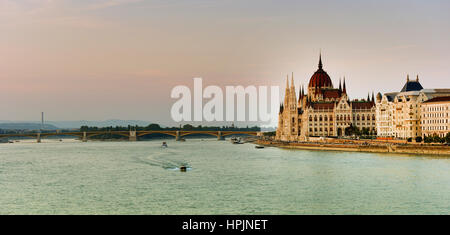 Budapest parliament at sunset near the Danube river - Stock Photo
