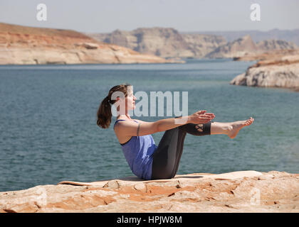 woman practicing yoga by lake - Stock Photo