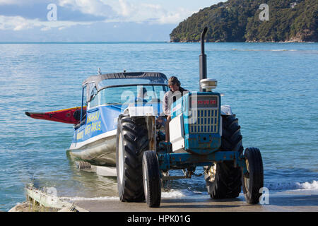 Marahau, Tasman, New Zealand. Tractor towing typical Abel Tasman National Park water taxi, kayak strapped to the - Stock Photo