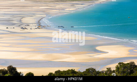 Marahau, Tasman, New Zealand. Panoramic view over Sandy Bay at low tide, water taxi approaching the beach. - Stock Photo