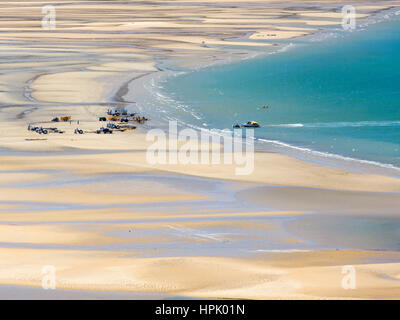 Marahau, Tasman, New Zealand. View over Sandy Bay at low tide, tractor pulling water taxi towards the beach. - Stock Photo
