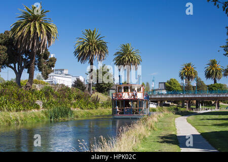 Blenheim, Marlborough, New Zealand. View along the palm-lined Taylor River, Marlborough's River Queen heading downstream. - Stock Photo