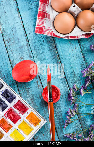 top view of eggs for coloring, paints and paintbrush on table for Easter - Stock Photo