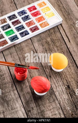 high angle view of colored eggs, paintbrush and paints for Easter