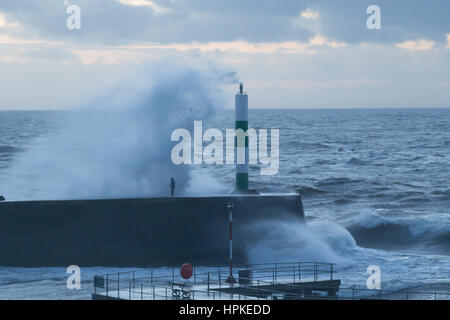 A man risking standing on a jetty as the big waves crash over him during storm Doris - Stock Photo