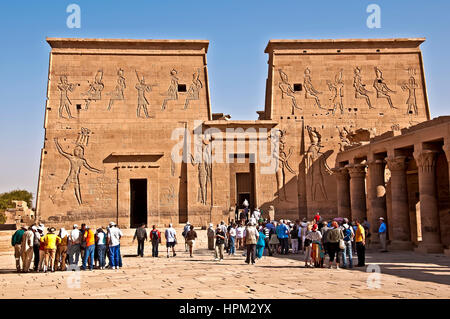 Groups of tourists in front of main entrance of Philae Temple, or Temple of Isis on Philae Island - Stock Photo