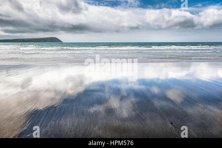 Wet sand on an empty beach reflecting the light cloudy blue sky - Stock Photo