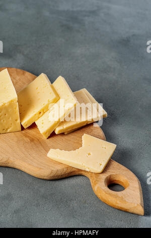 Hard cheese sliced on a wooden board home. Cheese for lunch. Gray background in the background. The cheese has small - Stock Photo