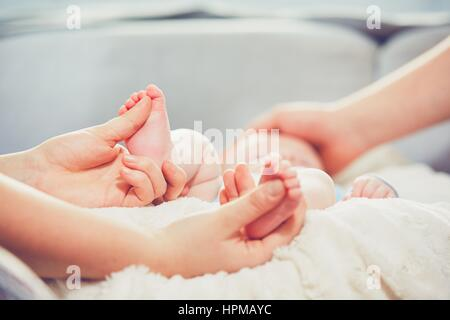 Touch of the parent love. Couple caress their little baby in the bed. - Stock Photo