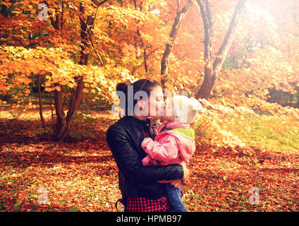 Happy kissing mother and daughter in autumn park - Stock Photo
