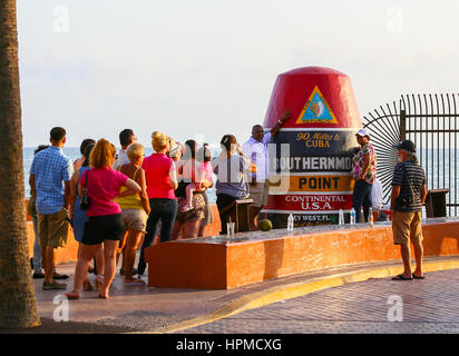 Key West, USA - May 10, 2015: People standing in line to take a picture of themselves at the replica of a buoy claiming - Stock Photo
