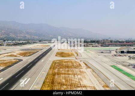 Burbank, USA - May 27, 2015: Aerial view of the airport with runways, a hangar and parked airplanes. - Stock Photo