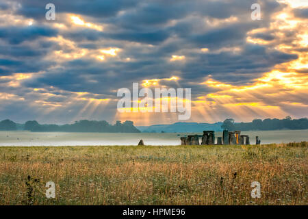 Amesbury, Wiltshire, United Kingdom - August 14, 2016: Cloudy sunrise over Stonehenge - prehistoric megalith monument - Stock Photo