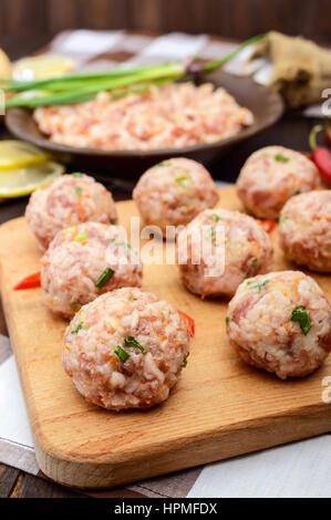 Raw meat balls, ready for cooking on a cutting board. - Stock Photo