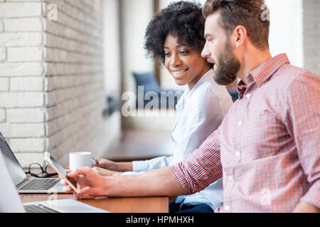 Coworkers working with laptop indoors - Stock Photo