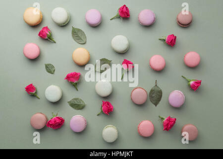 Macarons flat lay withroses and leaves on green background. Top view - Stock Photo