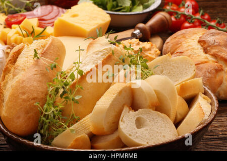 Fresh baguette and bread with herbs on rustic wooden board - Stock Photo