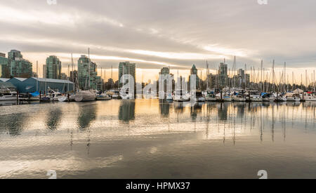 Vancouver, Canada - January 28, 2017: Vancouver city skyline with boats in harbour at sunset - Stock Photo