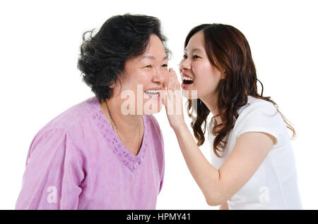 Portrait of Asian adult daughter sharing secrets to her senior mother, isolated on white background. - Stock Photo
